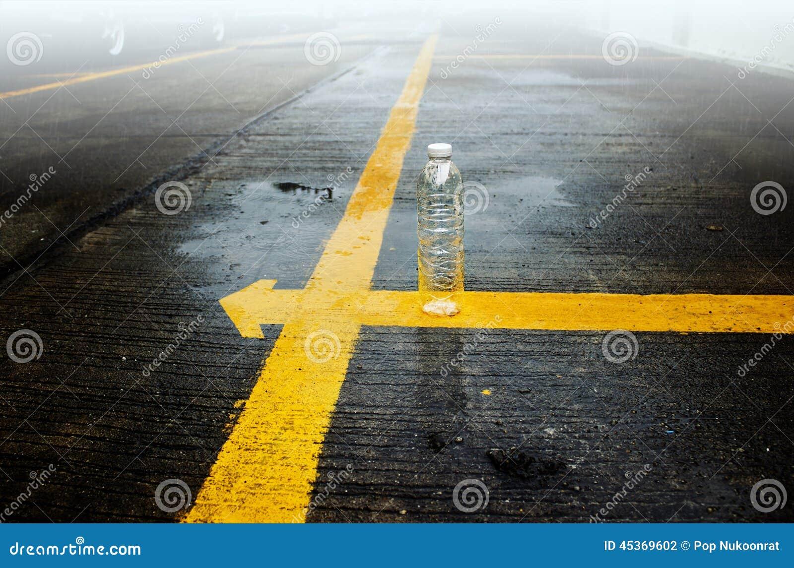 Bouteille vide sur la ligne jaune dans la pluie et le brouillard
