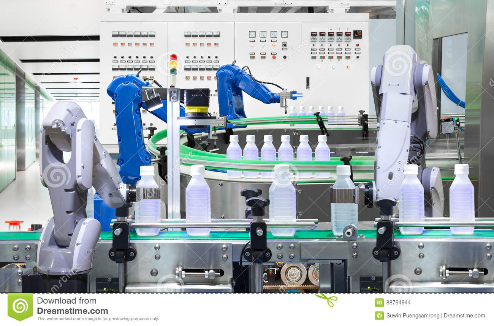 Bouteilles d eau robotiques de participation de bras sur la chaîne de production dans l usine,