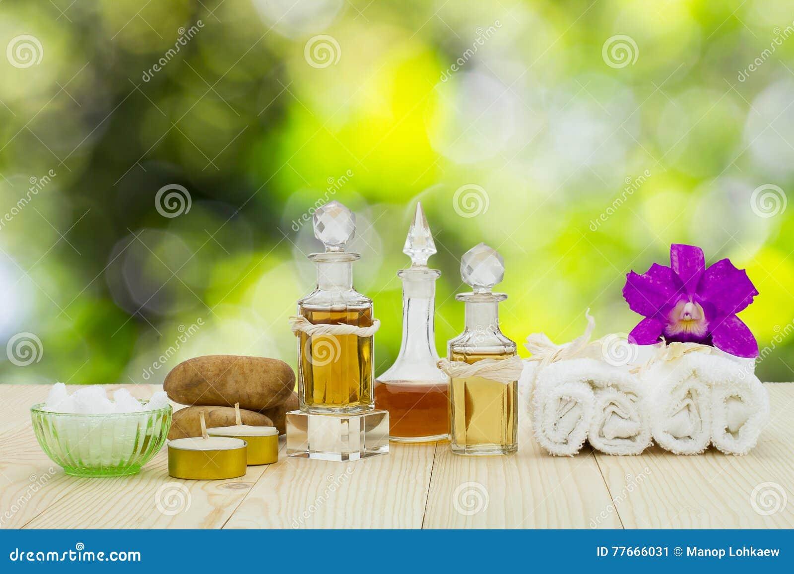 Bouteilles d huiles aromatiques avec les bougies, l orchidée rose, les pierres et la serviette blanche sur le plancher en bois su