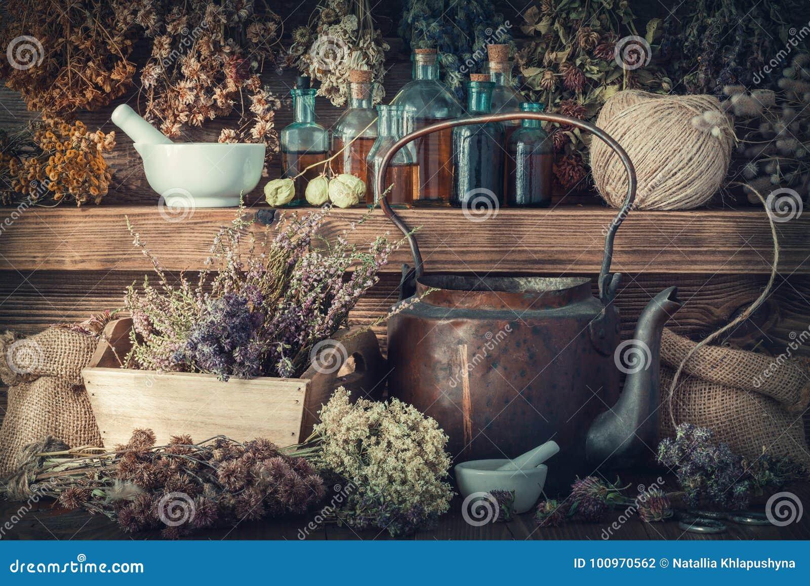 Bouteilles de teinture, herbes saines, mortier, drogues curatives, vieille bouilloire de thé sur l étagère en bois