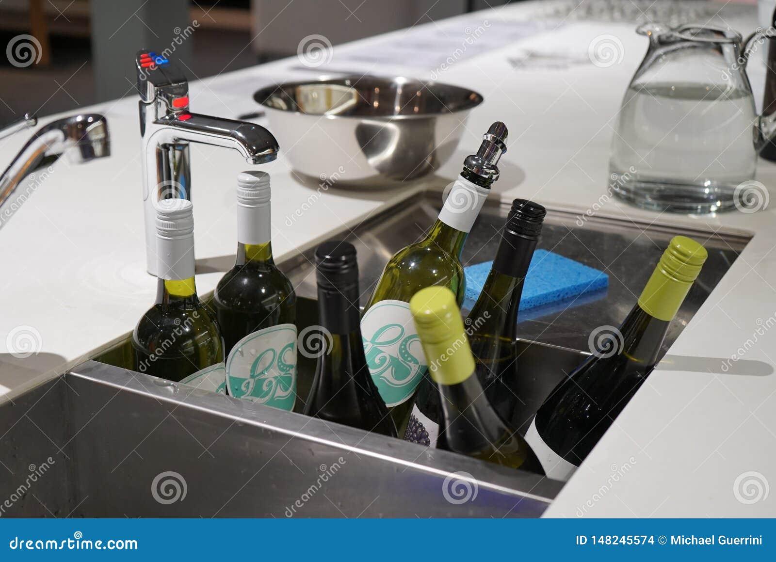 Bouteilles de vin étant refroidi dans un bain d évier complètement de glace et de l eau