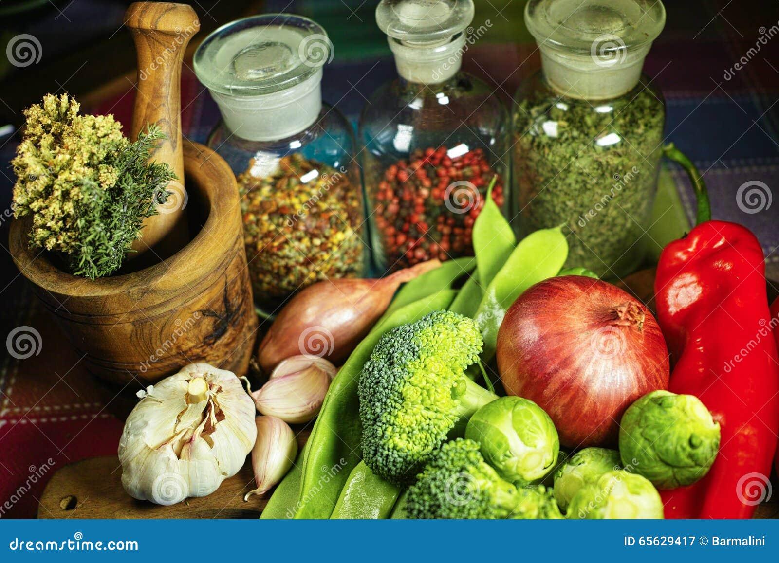 Bouteilles en verre avec des épices, des légumes rouges et verts frais, brocoli, tomates, ail, oignon