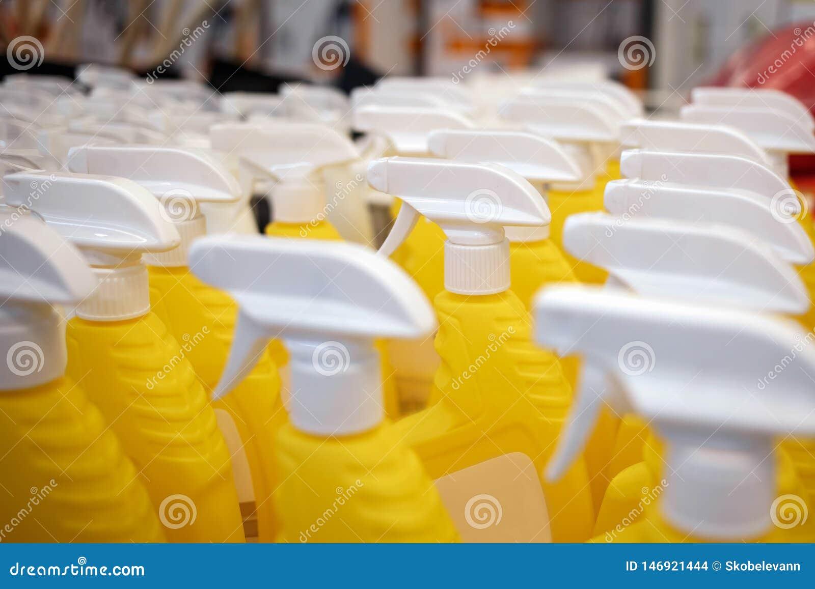 Bouteilles jaunes dans le magasin Pulvérisateurs pour l eau Les beaux pulvérisateurs sont sur les étagères de supermarché