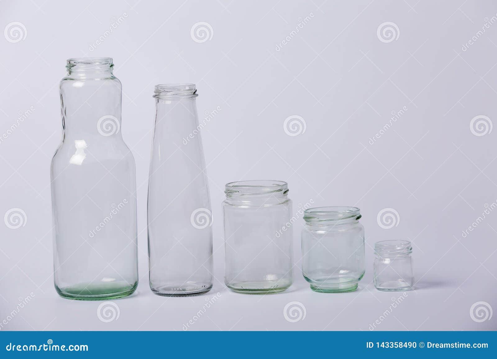 Bouteilles transparentes en verre Bouteilles transparentes en verre de tailles différentes de grand à petit sur un fond blanc
