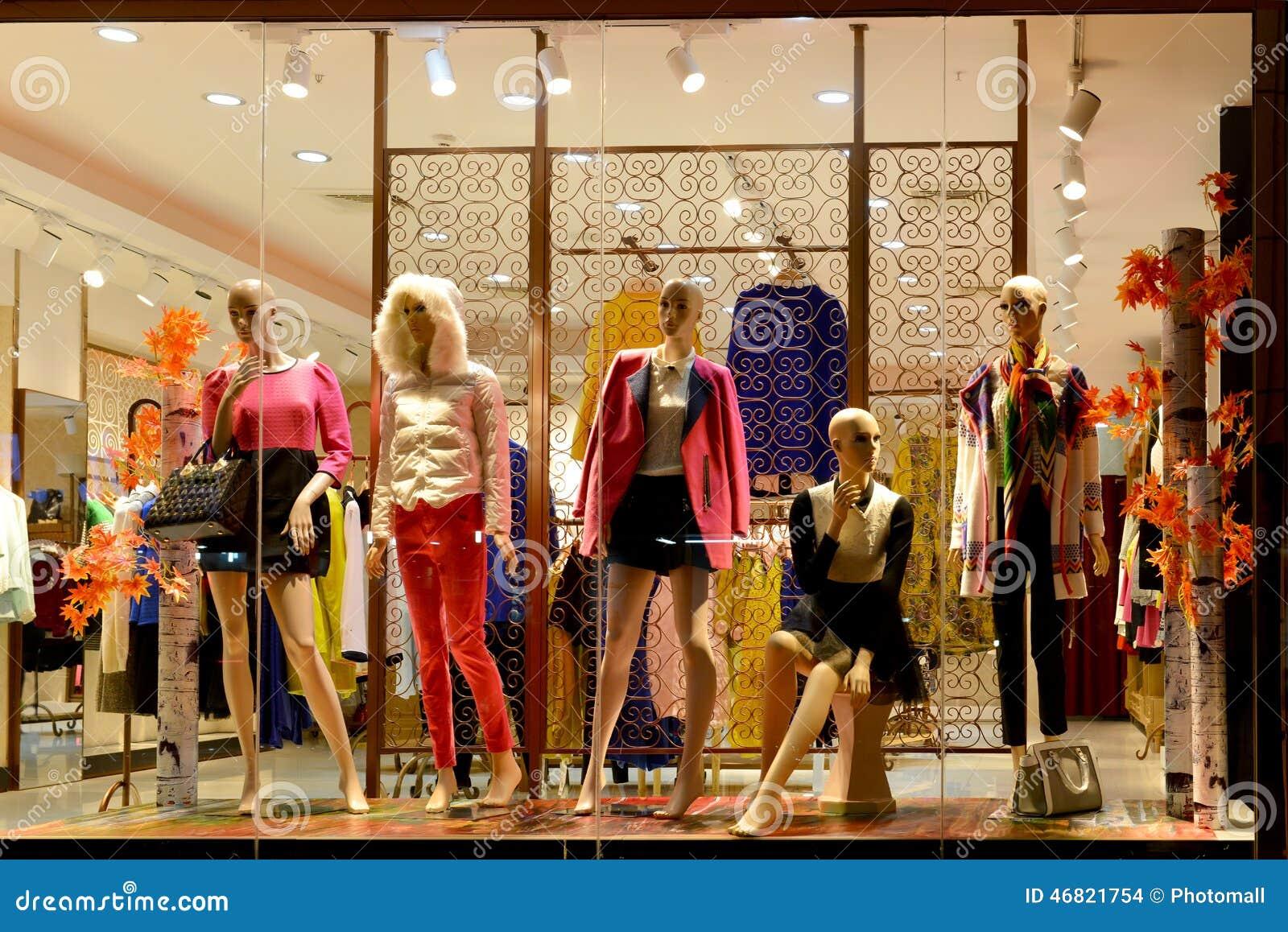 Boutiquefönstret, modeklädlagret, modelagerfönster i shoppinggallerian, klänning shoppar fönstret som tas på natten