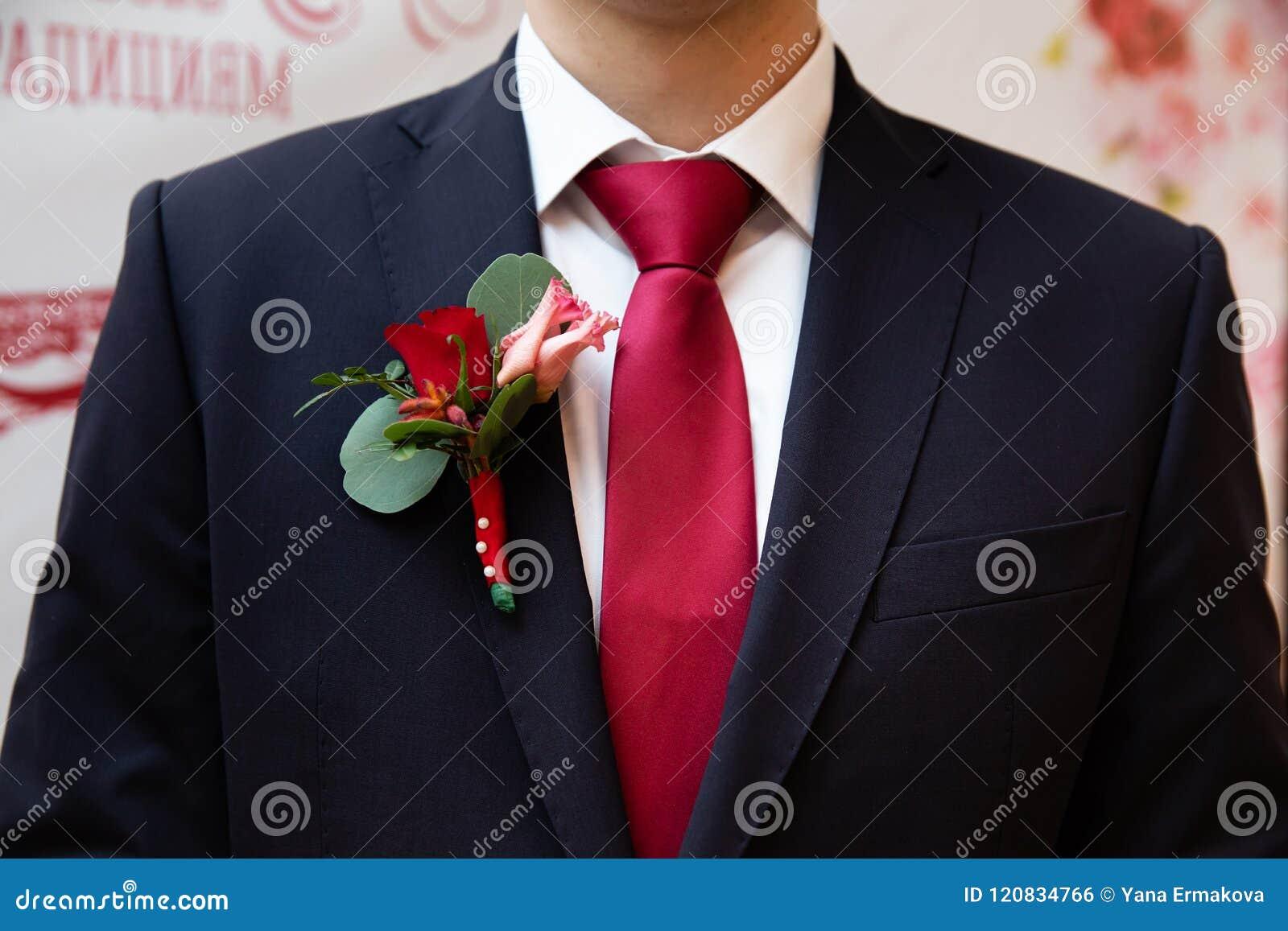 Boutonniere de la boda con la rosa del rojo en el traje del novio 05a86ed0d1a