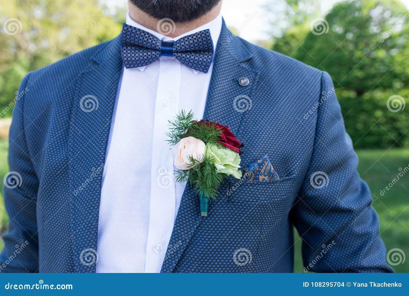 Boutonniere en la chaqueta del traje del novio Novio elegante en chaqueta  azul 31269ff2a5c