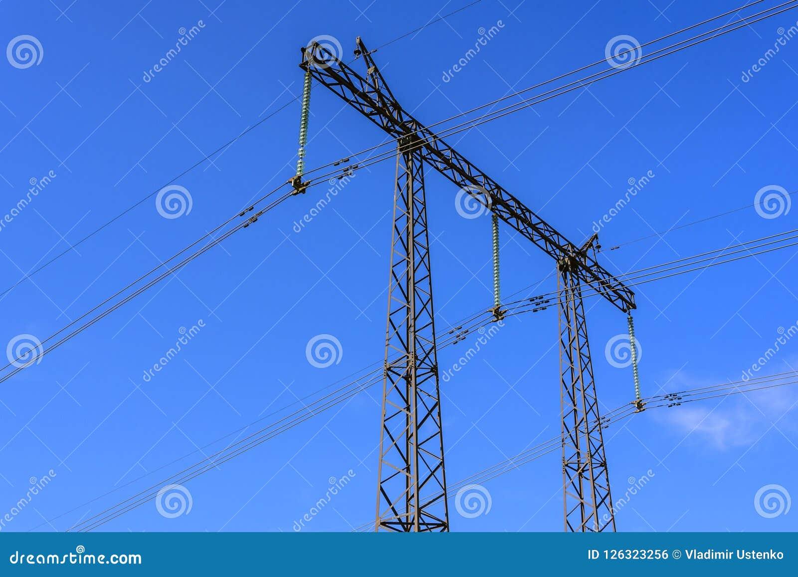 Bouw van een steun en draden van een close-up met hoog voltage van de machtslijn tegen een blauwe hemel
