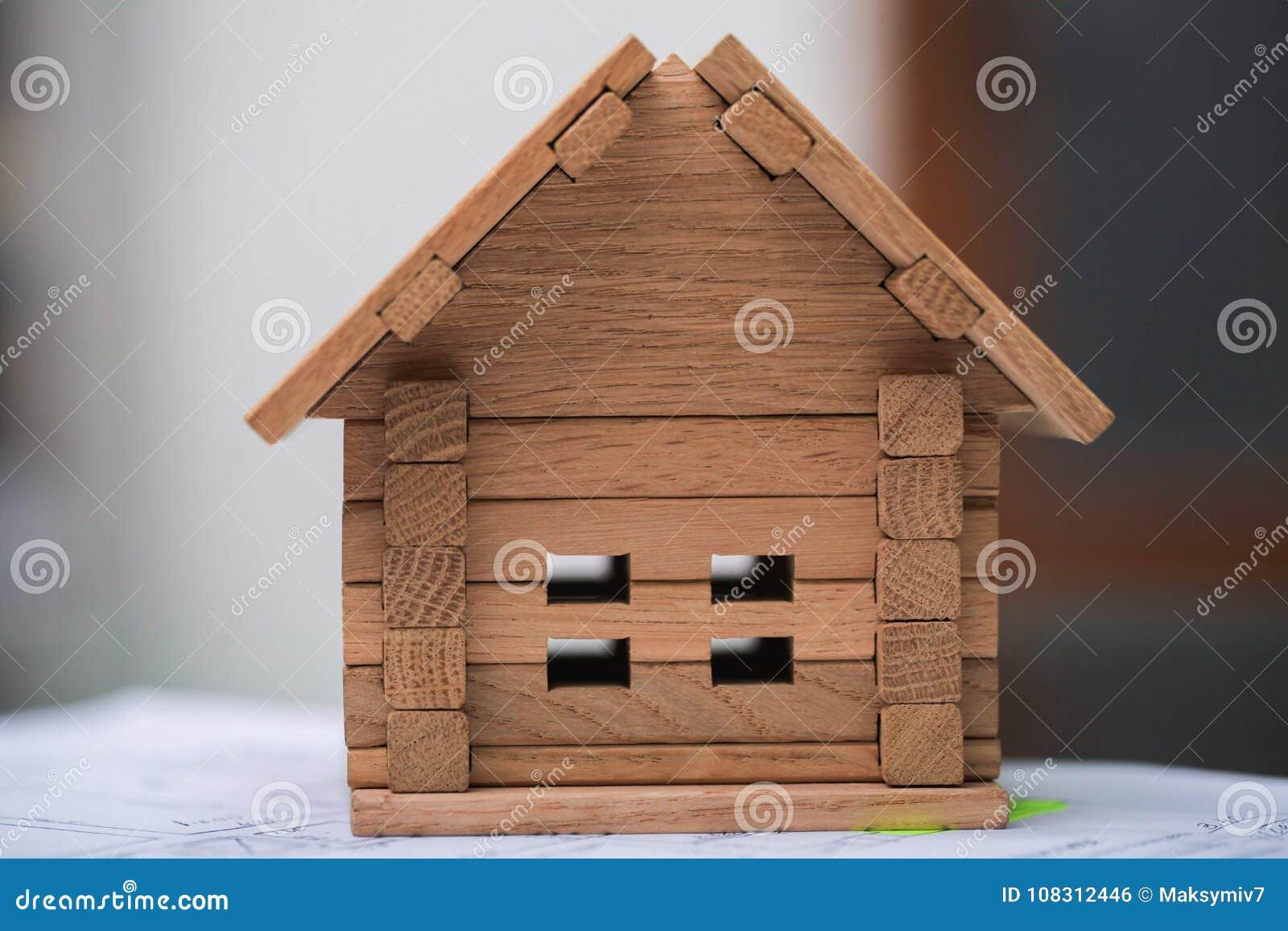 Bouwend huis op blauwdrukken met arbeider - bouwproject