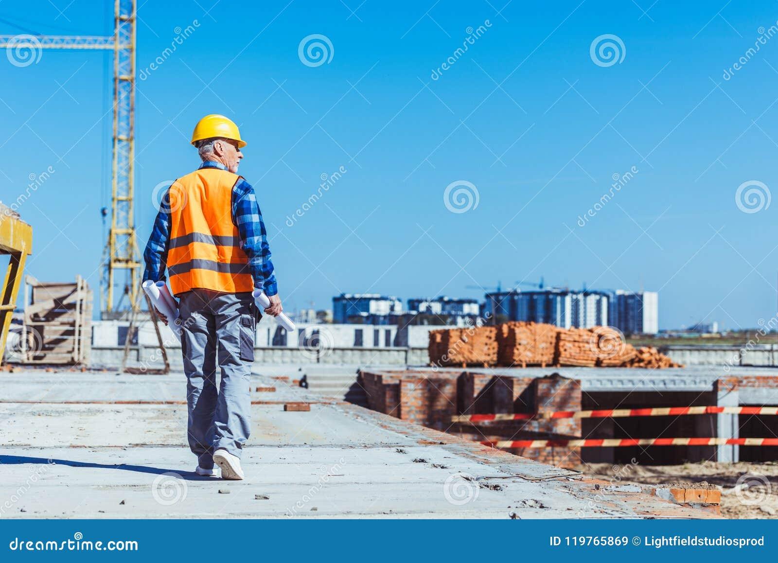 Bouwer in weerspiegelend vest en bouwvakker die over een bouwwerf met broodjes van plannen lopen