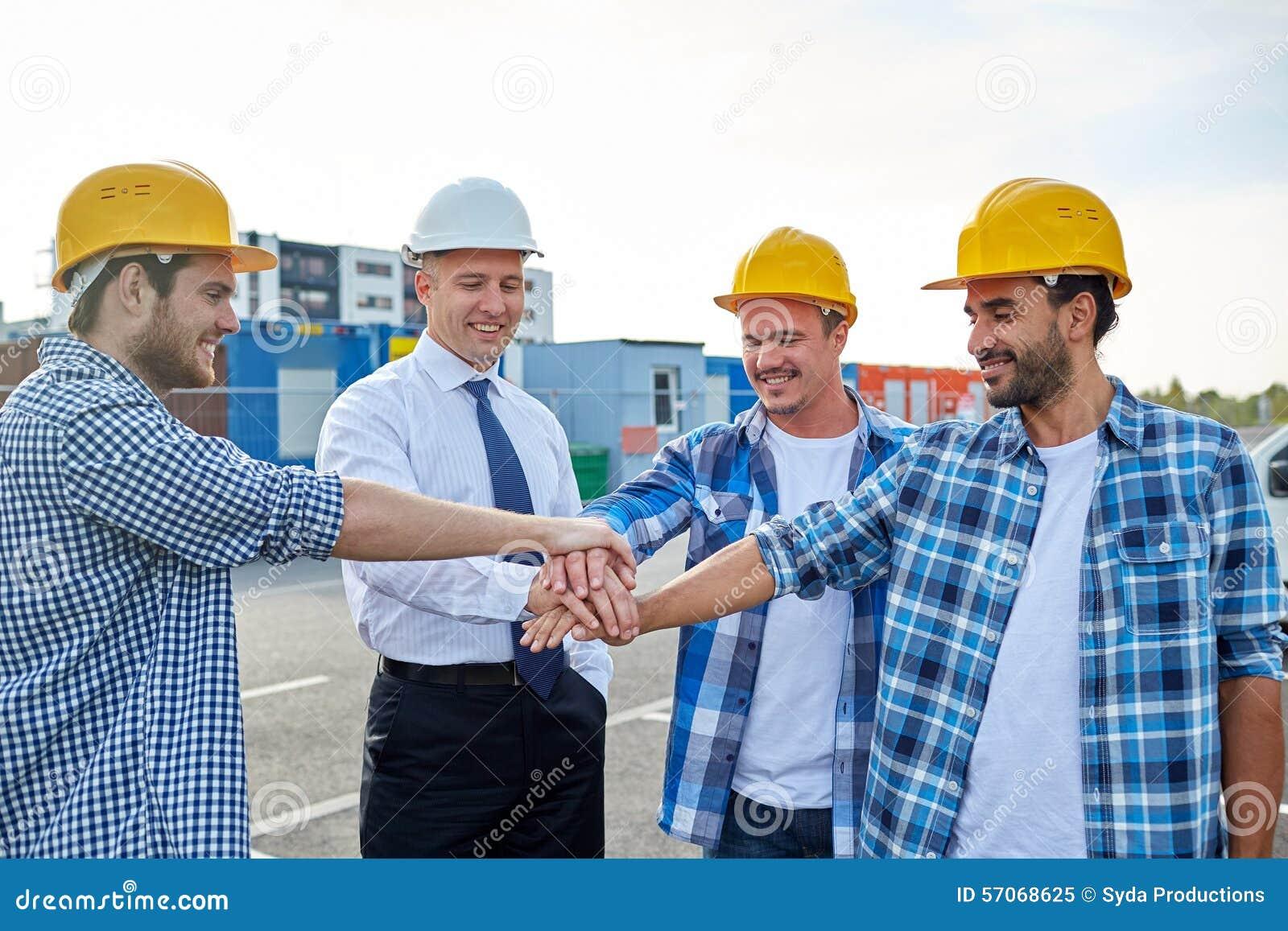 Bouwers en architecten met handen op bovenkant