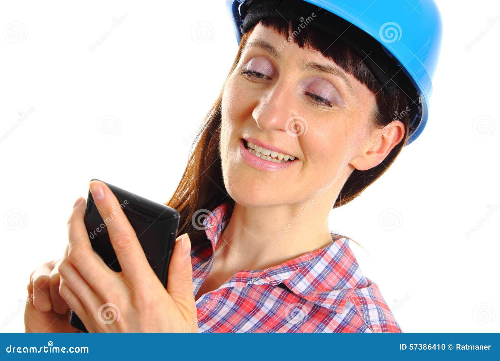 Bouwersvrouw in beschermende helm die mobiele telefoon met behulp van