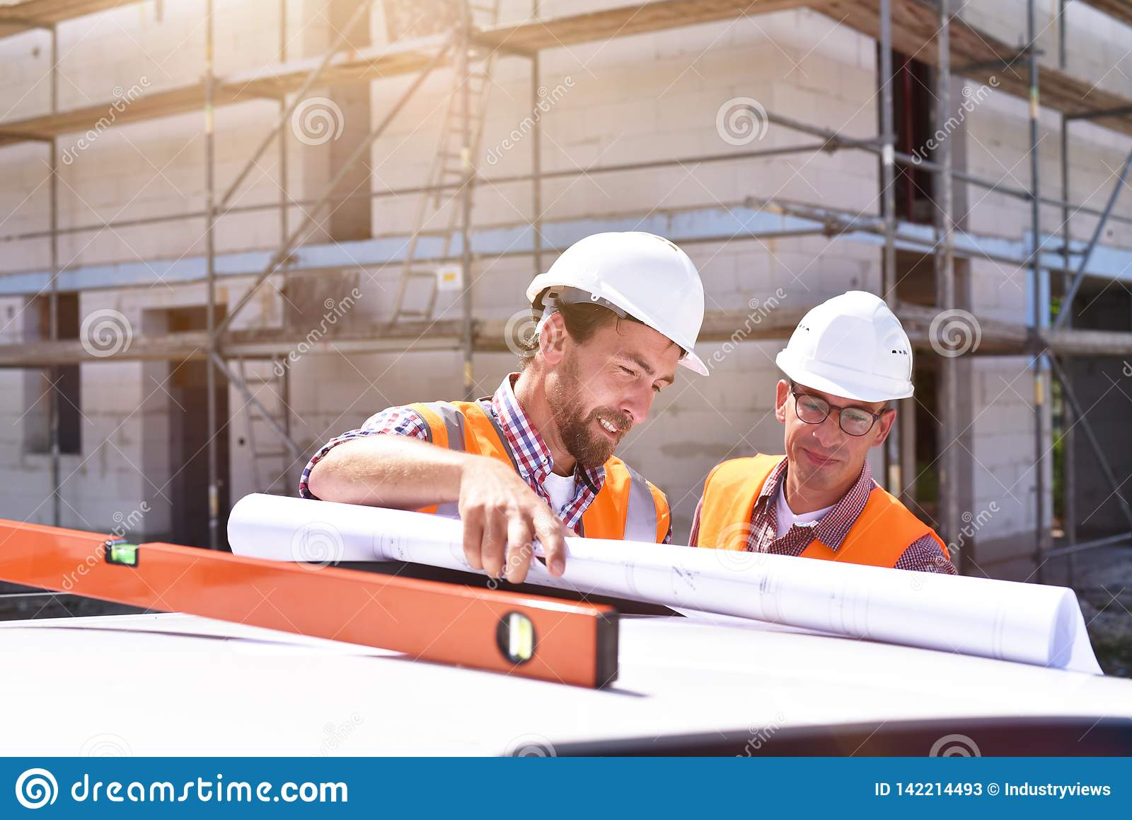 Bouwmanager en architect op plaats tijdens de bouw van een huis - planning en controle op plaats - groepswerk