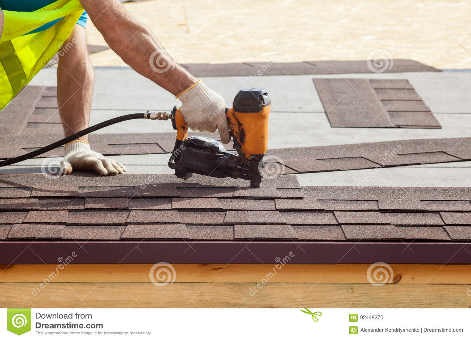 Bouwvakker die de dakspanen van het asfaltdakwerk met spijkerkanon zet op een nieuw kaderhuis