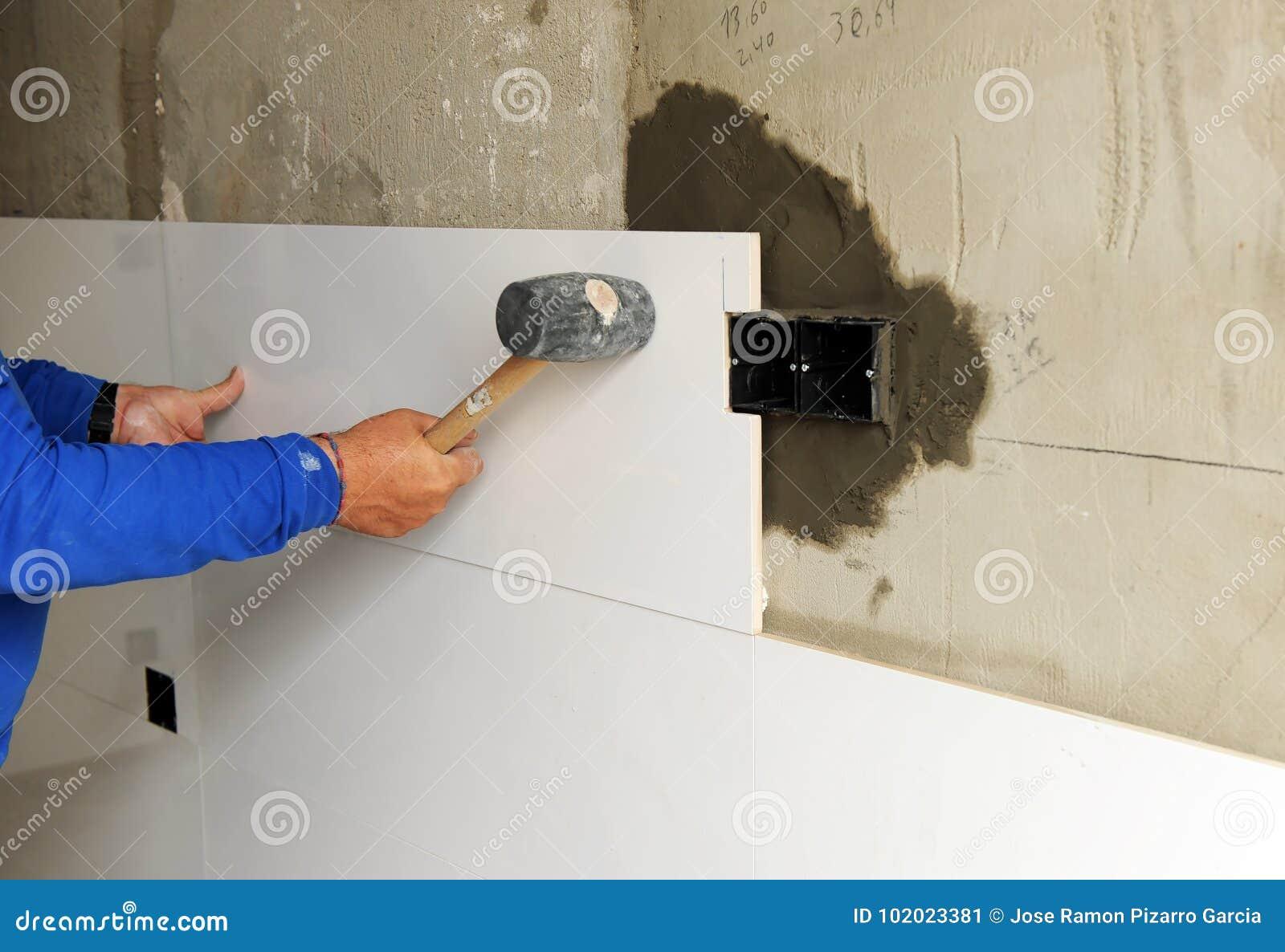 Tegels Keuken Witte : Bouwvakker die de witte tegels van het porseleinsteengoed in de