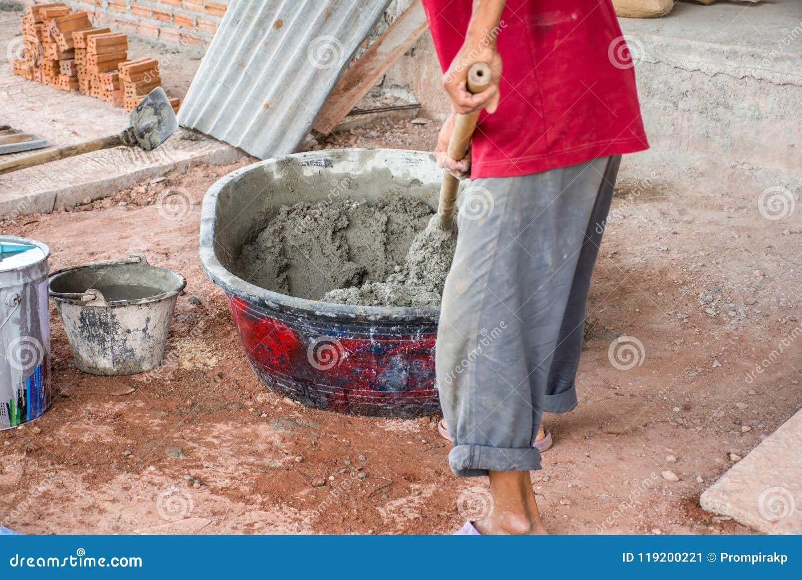 Bouwvakker die manueel beton in mixerdienblad mengen