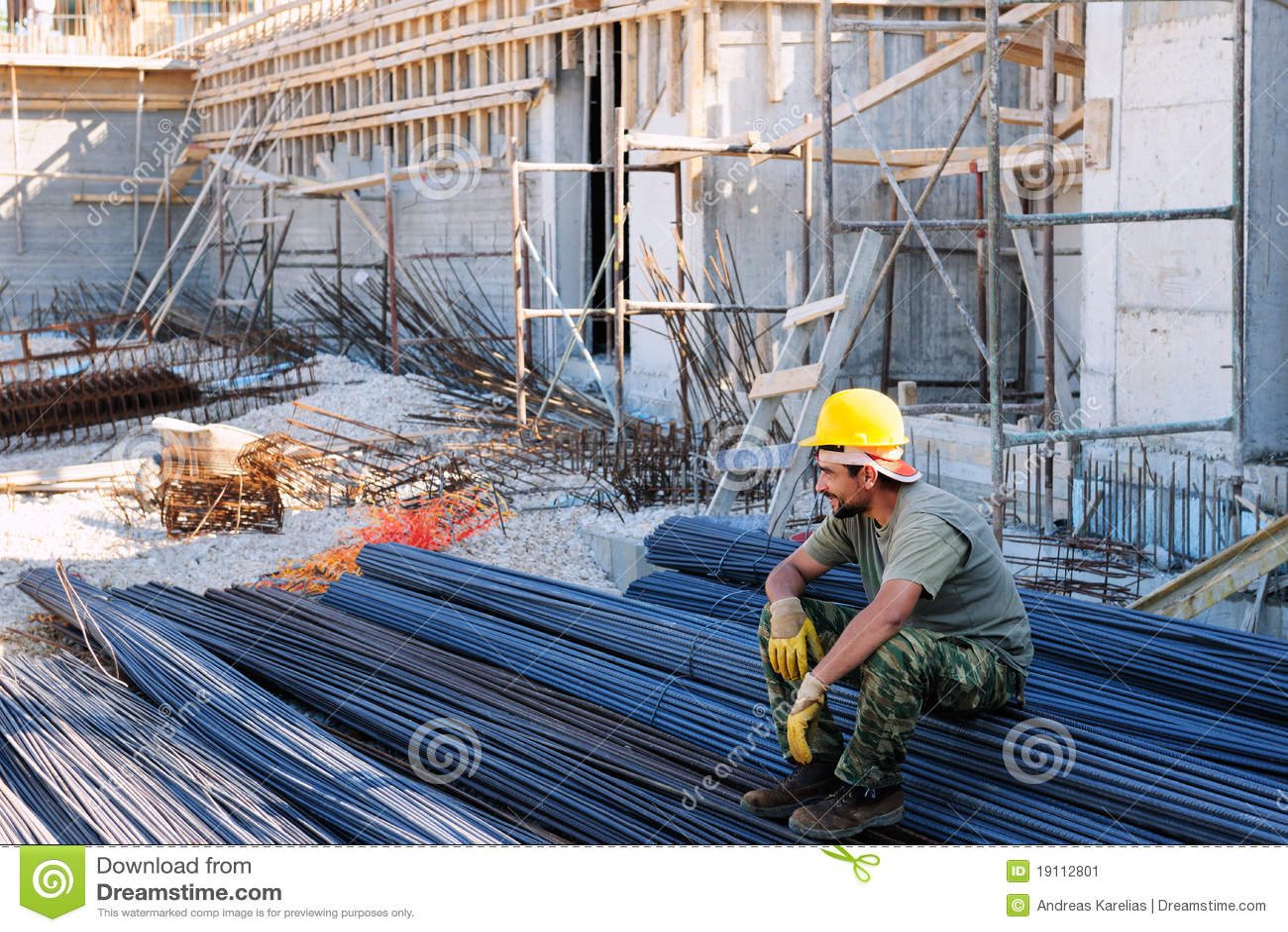 Bouwvakker die op staalstaven rust