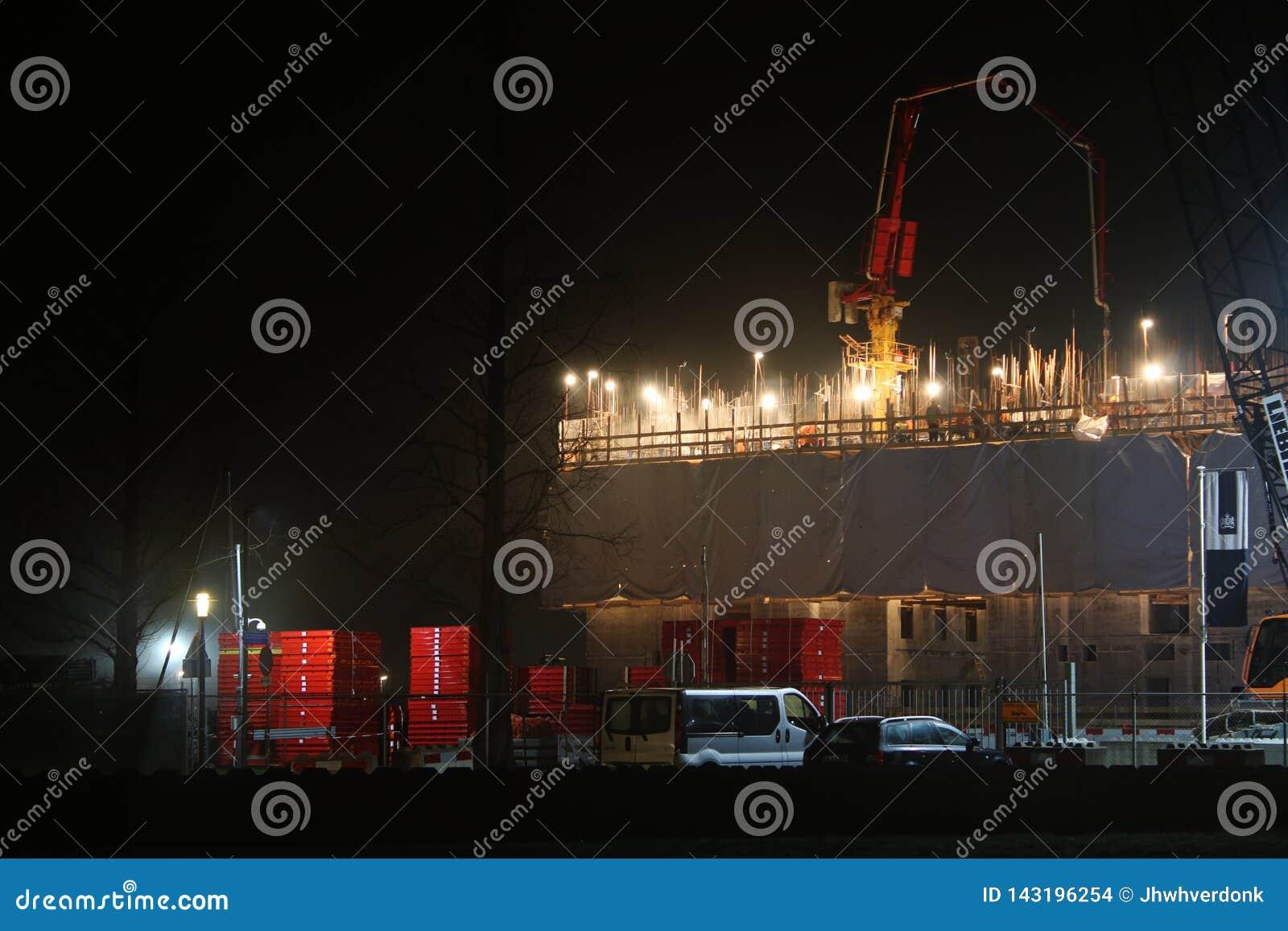 Bouwwerf met een groep bouwvakkers die aan een gebouw tijdens de nacht werken