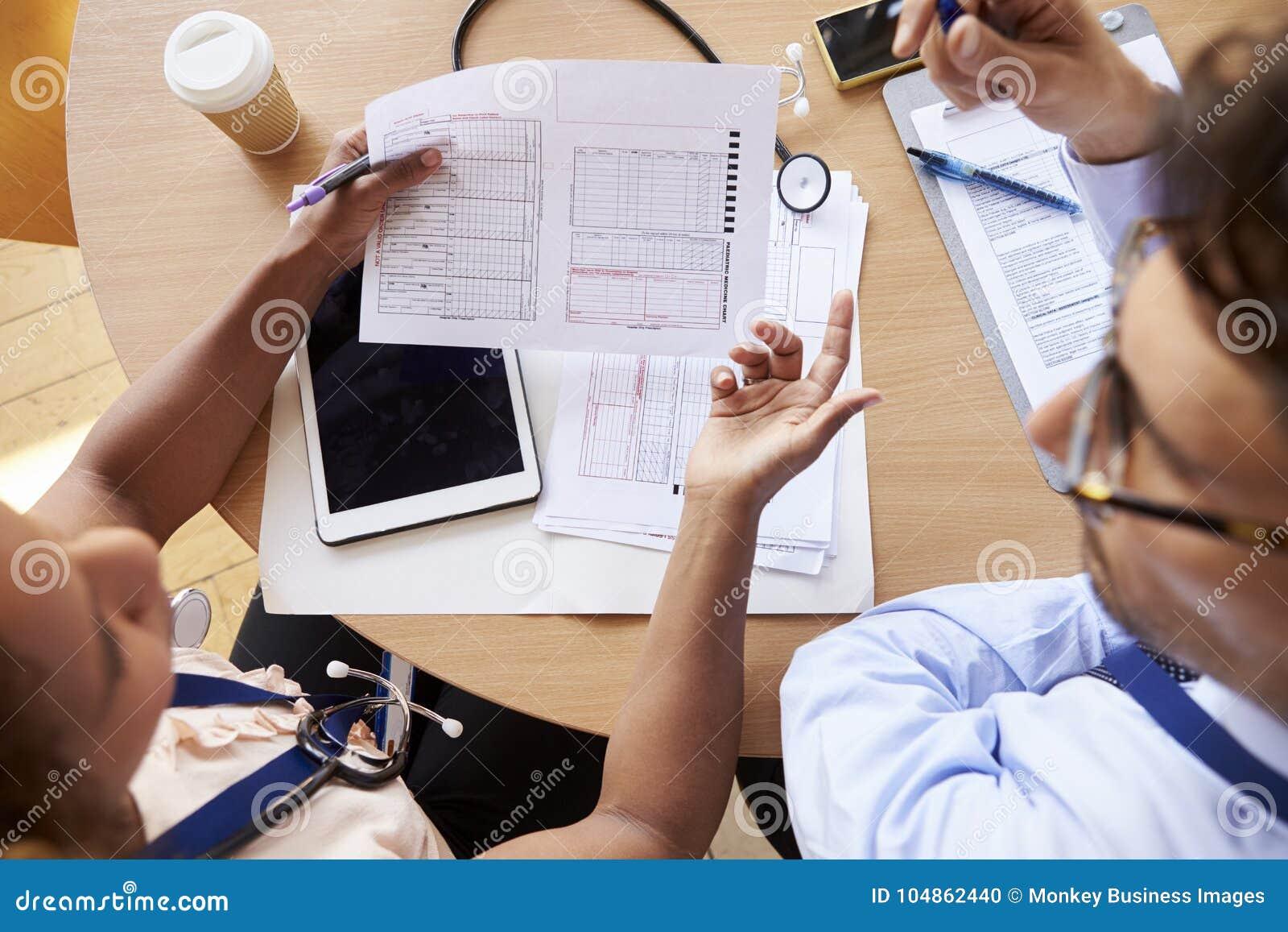 Boven geschoten van artsen in overleg over geduldige nota s