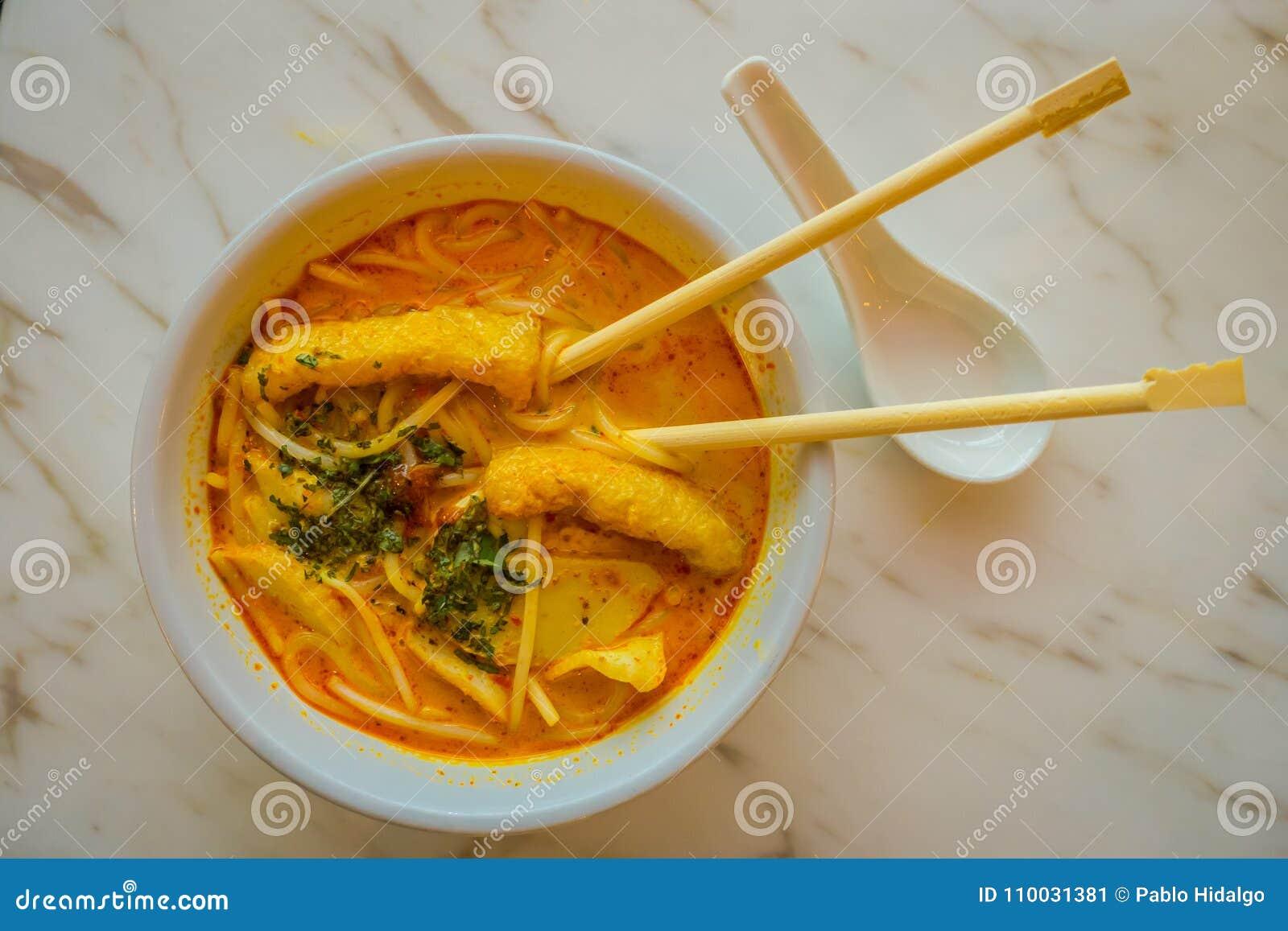 Boven mening van de rijstnoedel van penang asam laksa in witte kom met eetstokjes binnen de kom op witte lijst met kruidige visse