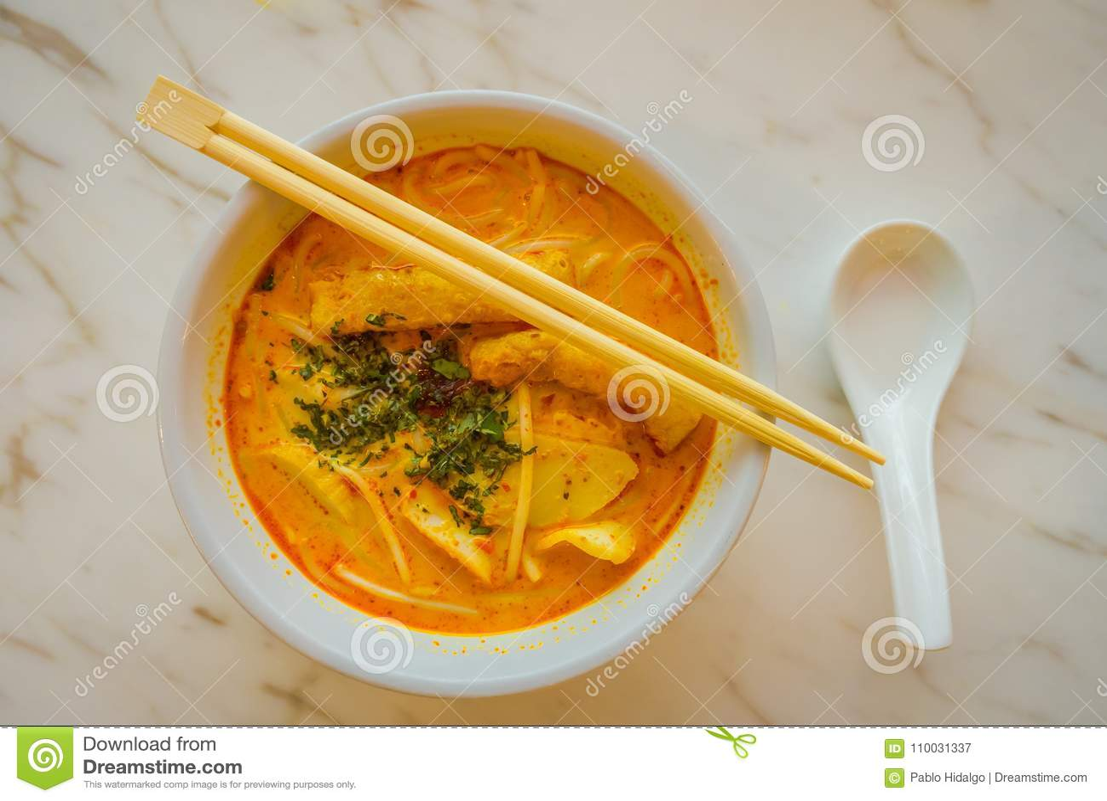 Boven mening van de rijstnoedel van penang asam laksa in witte kom met eetstokjes op witte lijst met de kruidige soep van de viss