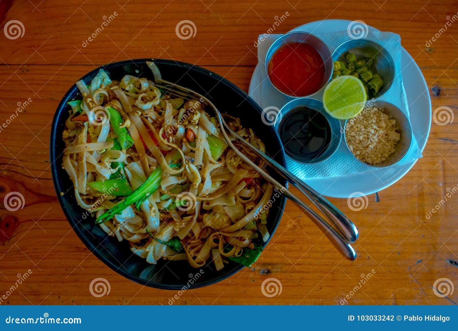 Boven mening van heerlijke Thaise noedel, met vier sausen binnen van een metaaldienblad iver een witte plaat in een houten lijst