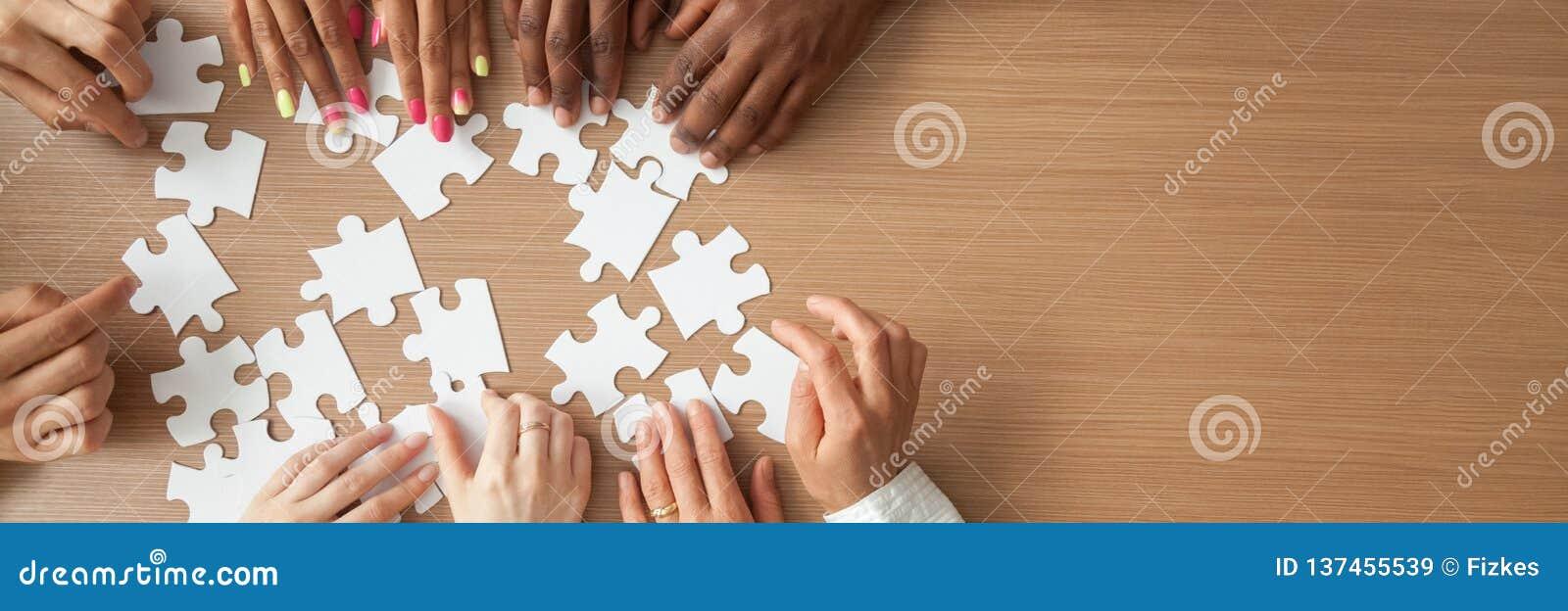 Boven panoramahanden van diverse mensen die puzzel assembleren