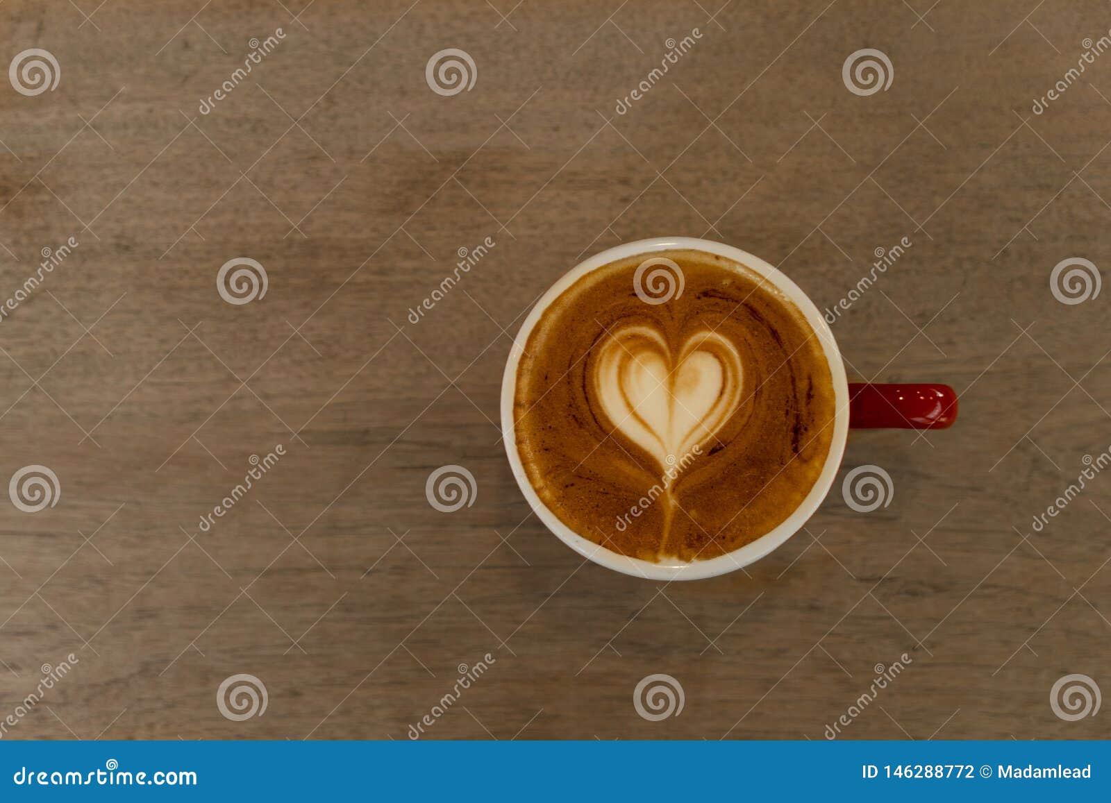 Bovenkant van de witte drank van de de cappuccinokoffie van de hartvorm hete in rode ceramische kop op houten lijstachtergrond