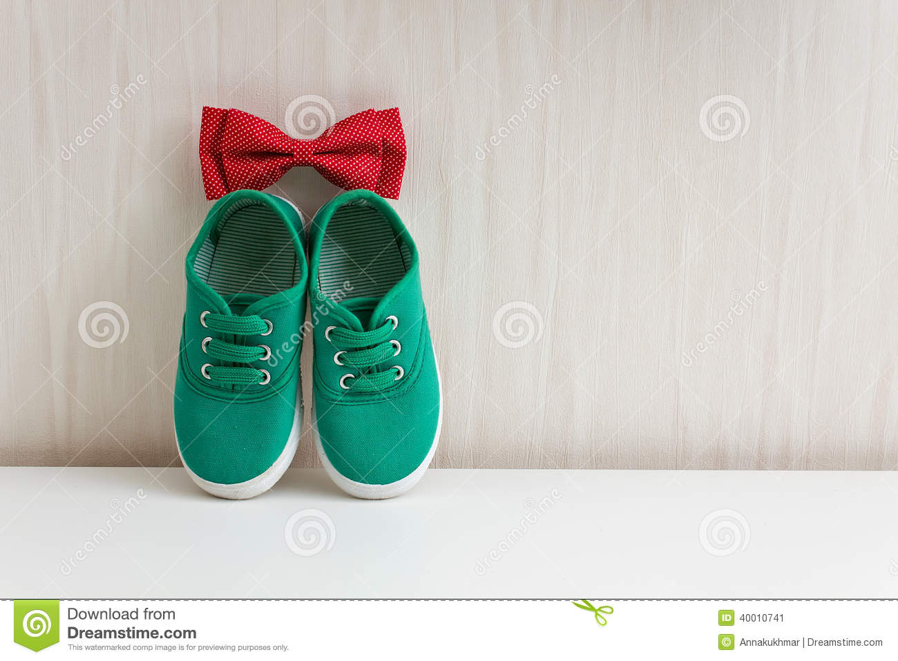 Bow tie and green shoes on background wall with wallpaper