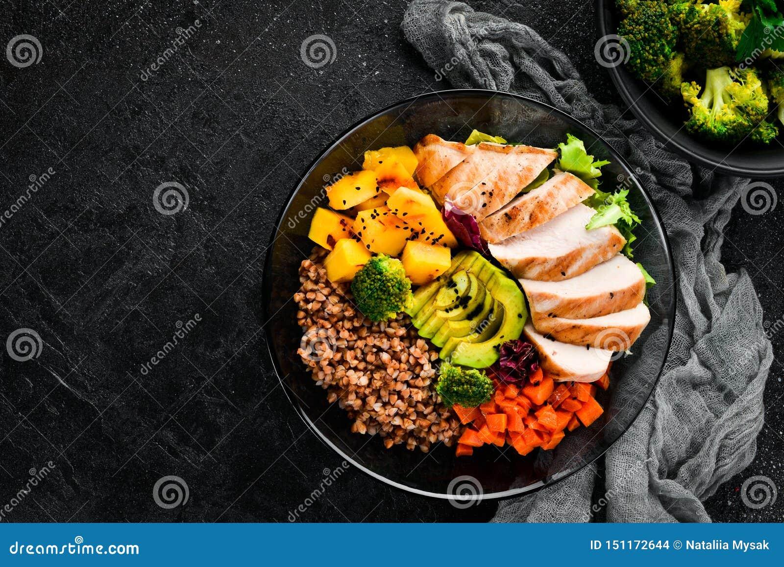 Bowl Buddha. Buckwheat, pumpkin, chicken fillet, avocado, carrots. On a black background.