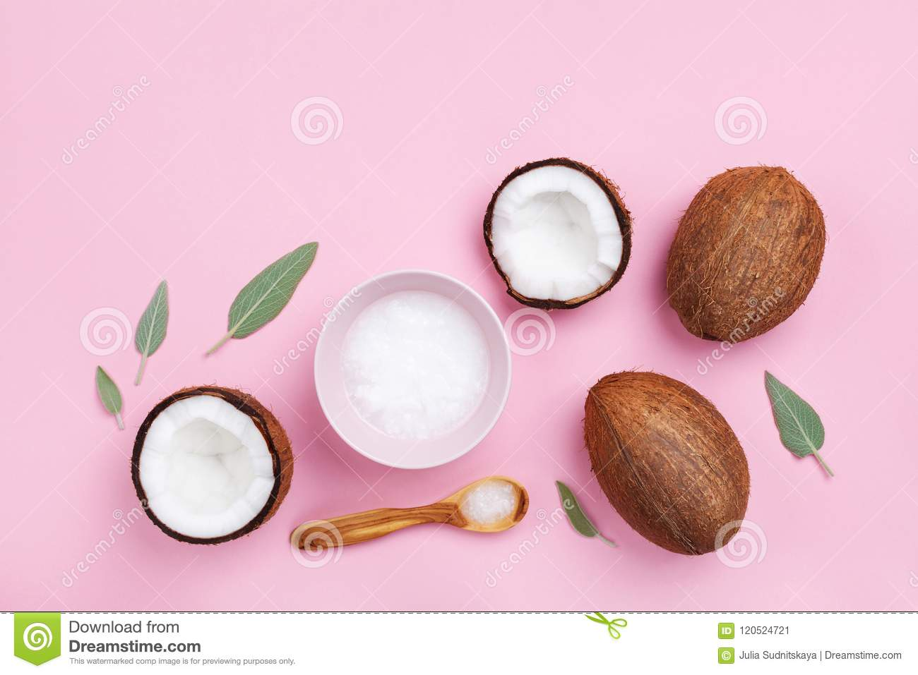 Bowl with coconut oil and fresh half of coconuts on pink table top view. Beauty and spa homemade cosmetic. Flat lay.