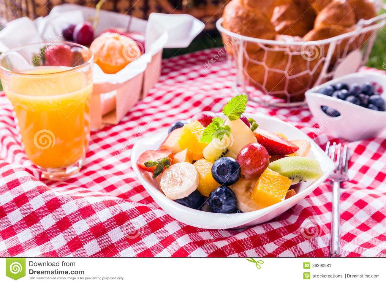 Bowl of fresh tropical fruit salad at a picnic served with a glass of ...
