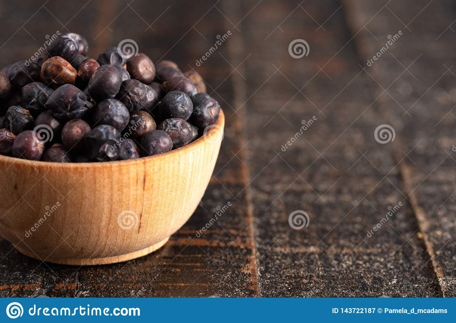 Bowl Full of Dried Juniper Berries on a Wooden Table
