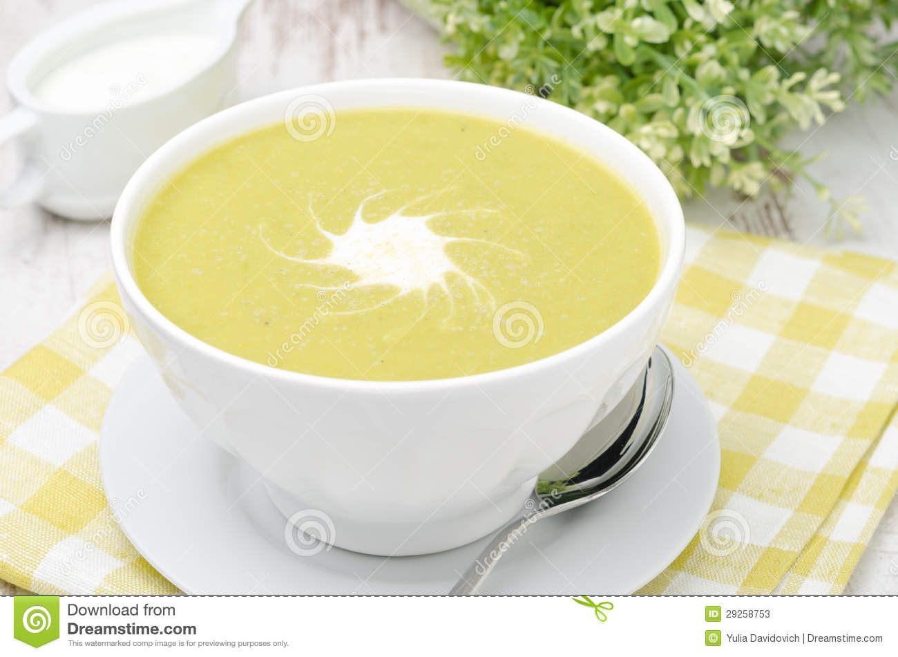 Bowl of green pea soup with ginger and cream in a white bowl, closeup ...