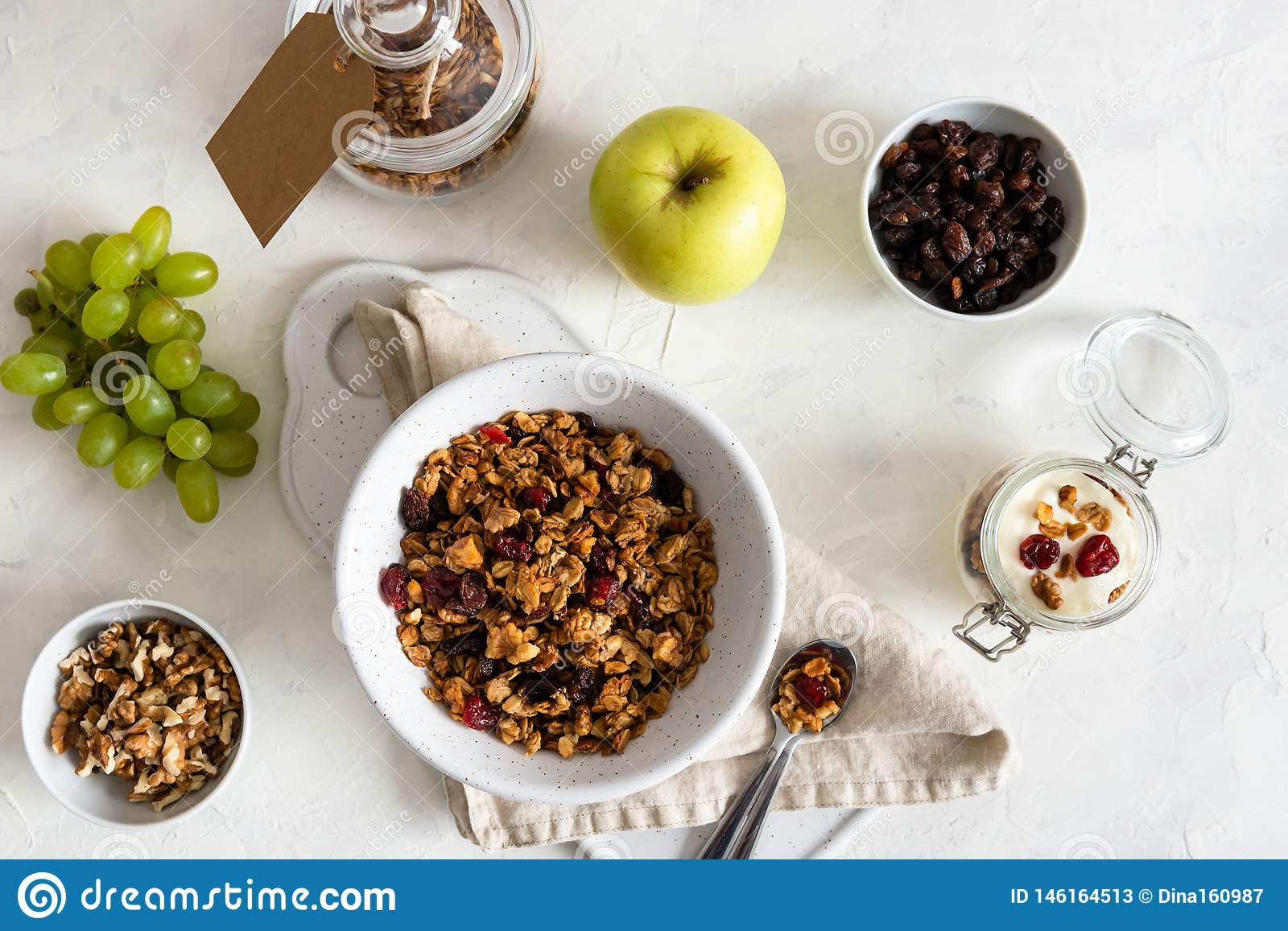 Bowl of homemade granola with nuts and fruits on white linen background. Top view. Healthy breakfast, dieting, nutrition