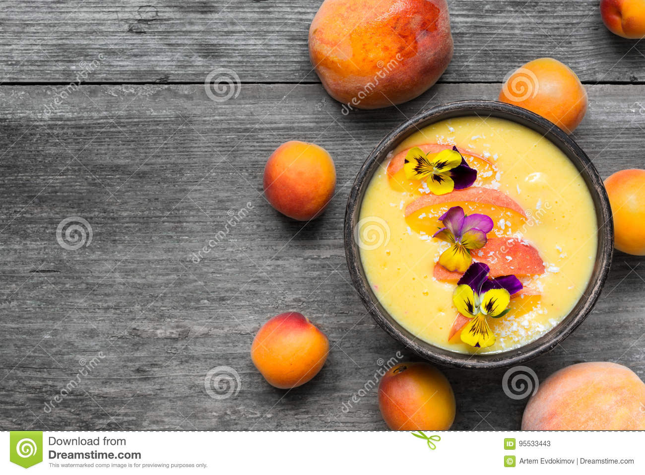 Bowl of homemade yellow smoothie with fresh mango, peaches and apricots