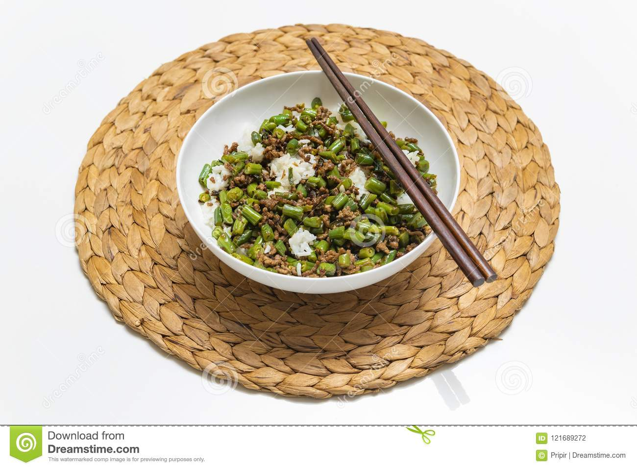 Bowl of minced beef with round beans and rice, with chopsticks on straw mat