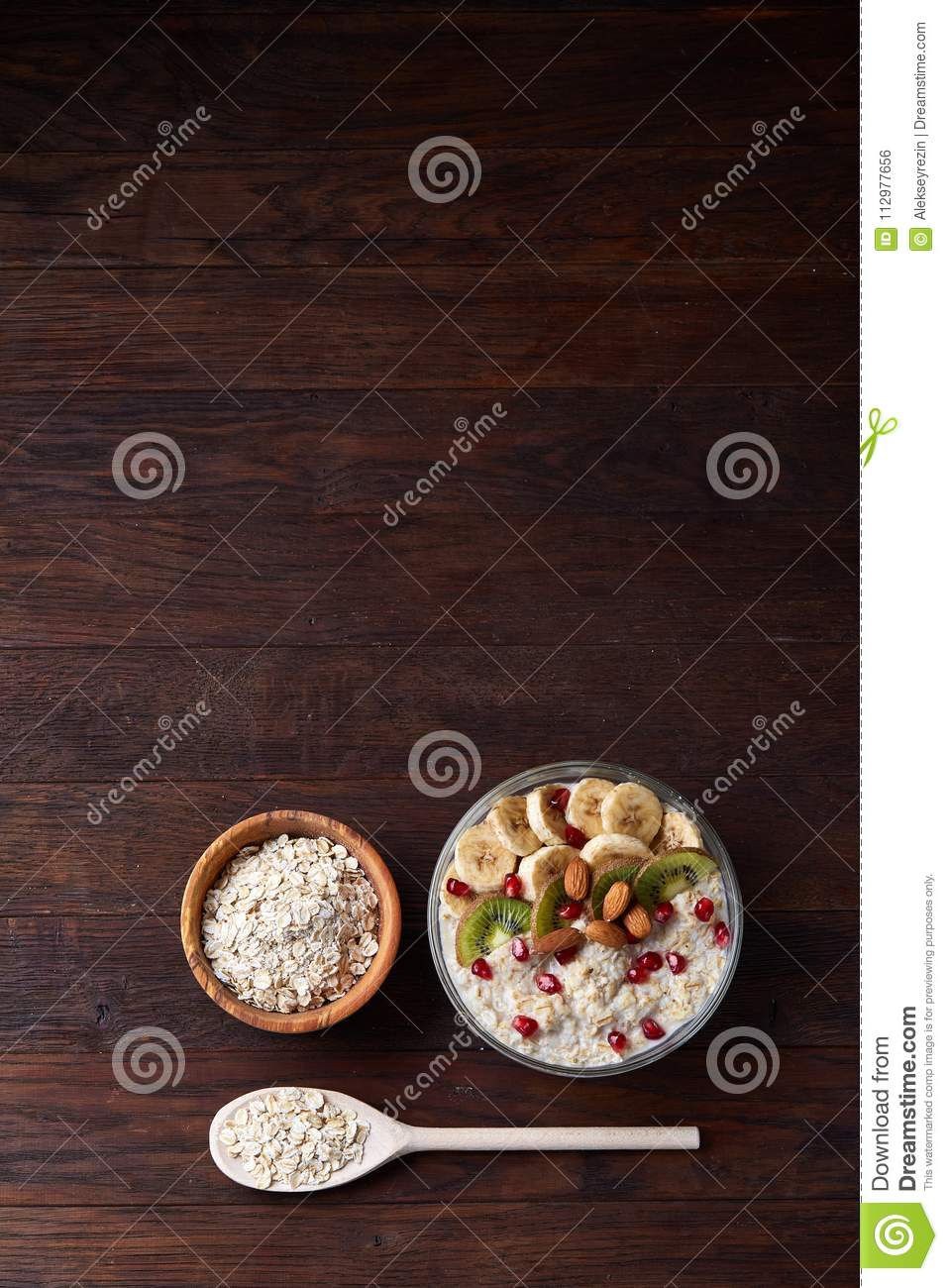 Bowl with oatmeal flakes served with fruits on wooden tray over rustic background, flat lay, selective focus