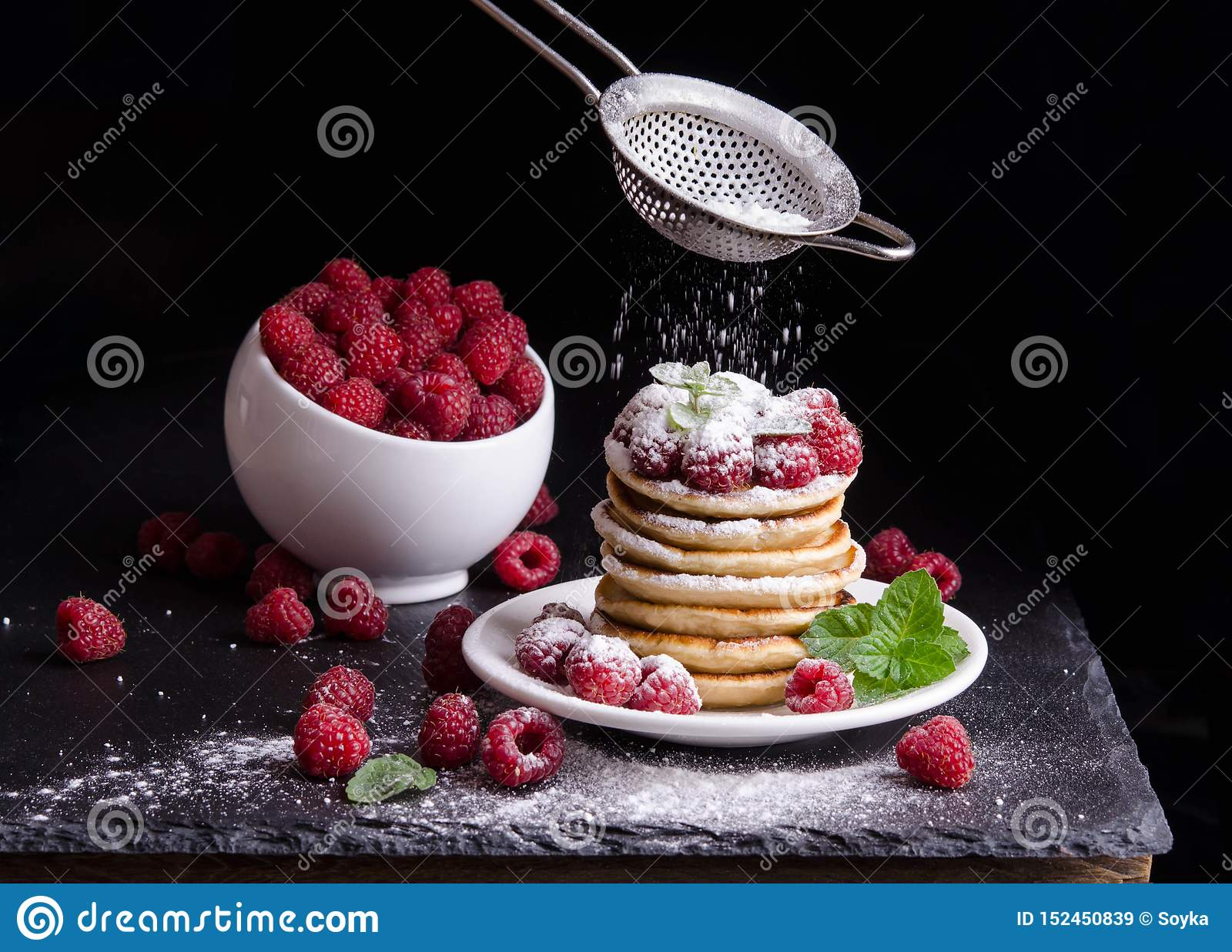 Bowl and  Pancakes with raspberries around
