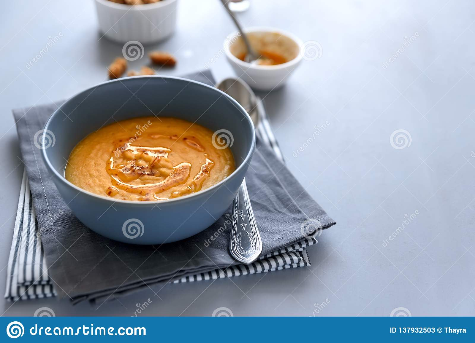 Bowl of red lentil soup on gray wooden background. Vegetarian food concept