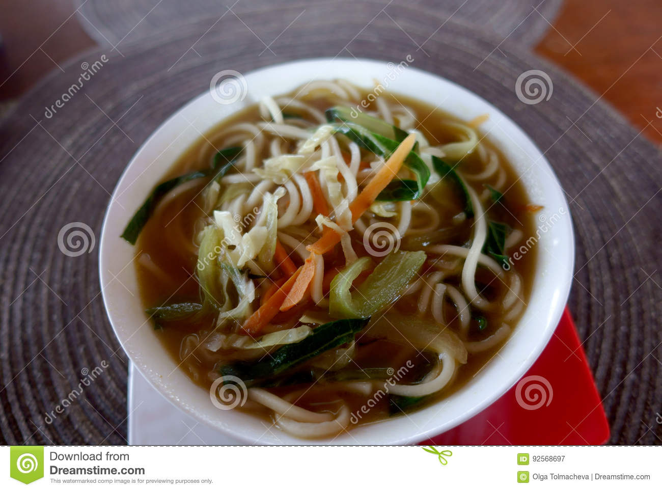 A bowl of soup with noodles and vegetables on a round napkin