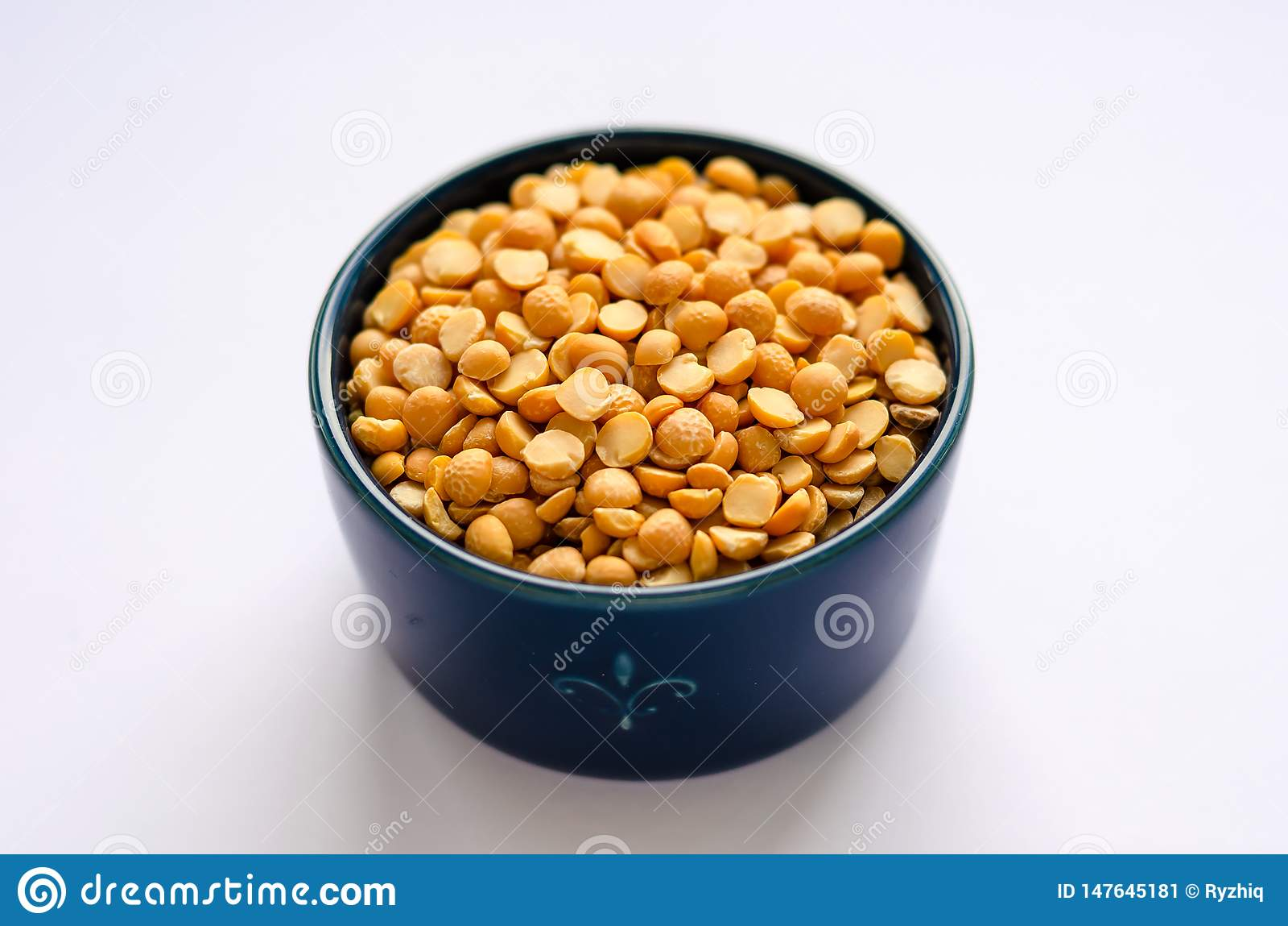 Bowl of yellow dried split peas on white background