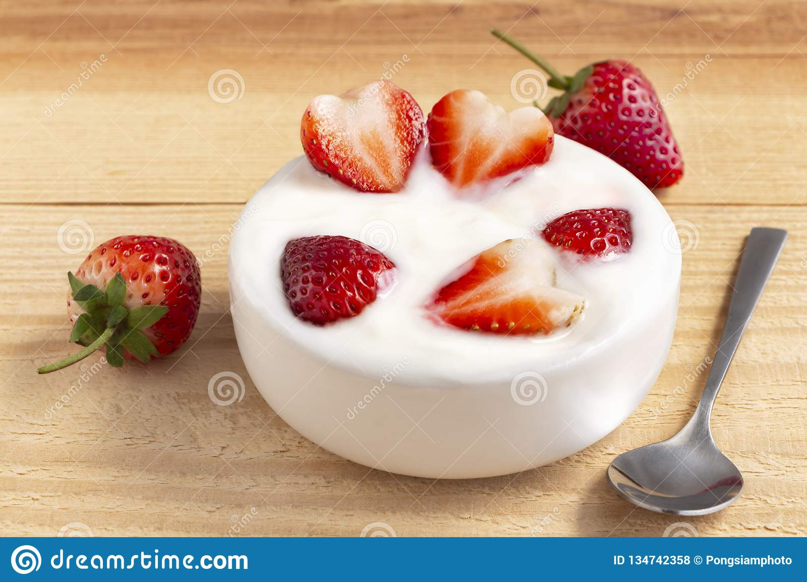 Bowl of yogurt and red fruit strawberry on the wood table. Yogurt made from milk fermented by added bacteria, often sweetened and
