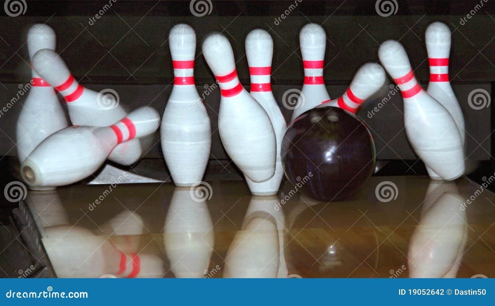 Bowlingspielkugel und fallende Stifte