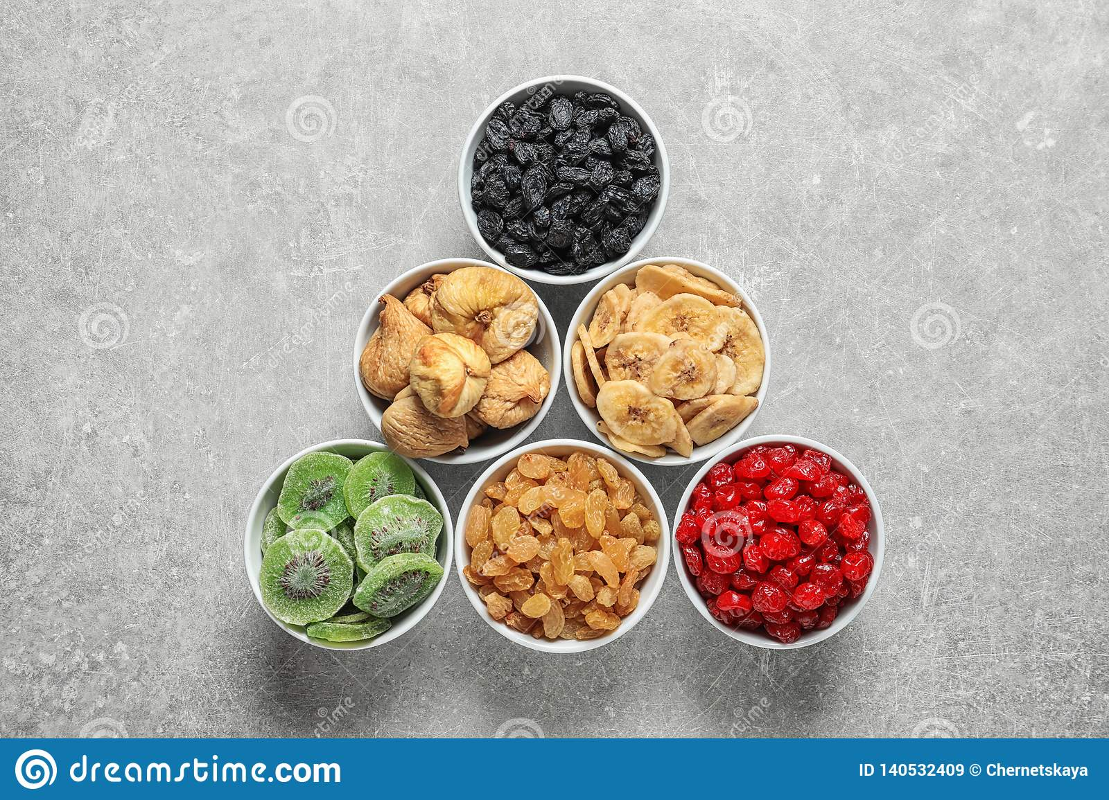 Bowls With Different Dried Fruits On Grey Background, Flat
