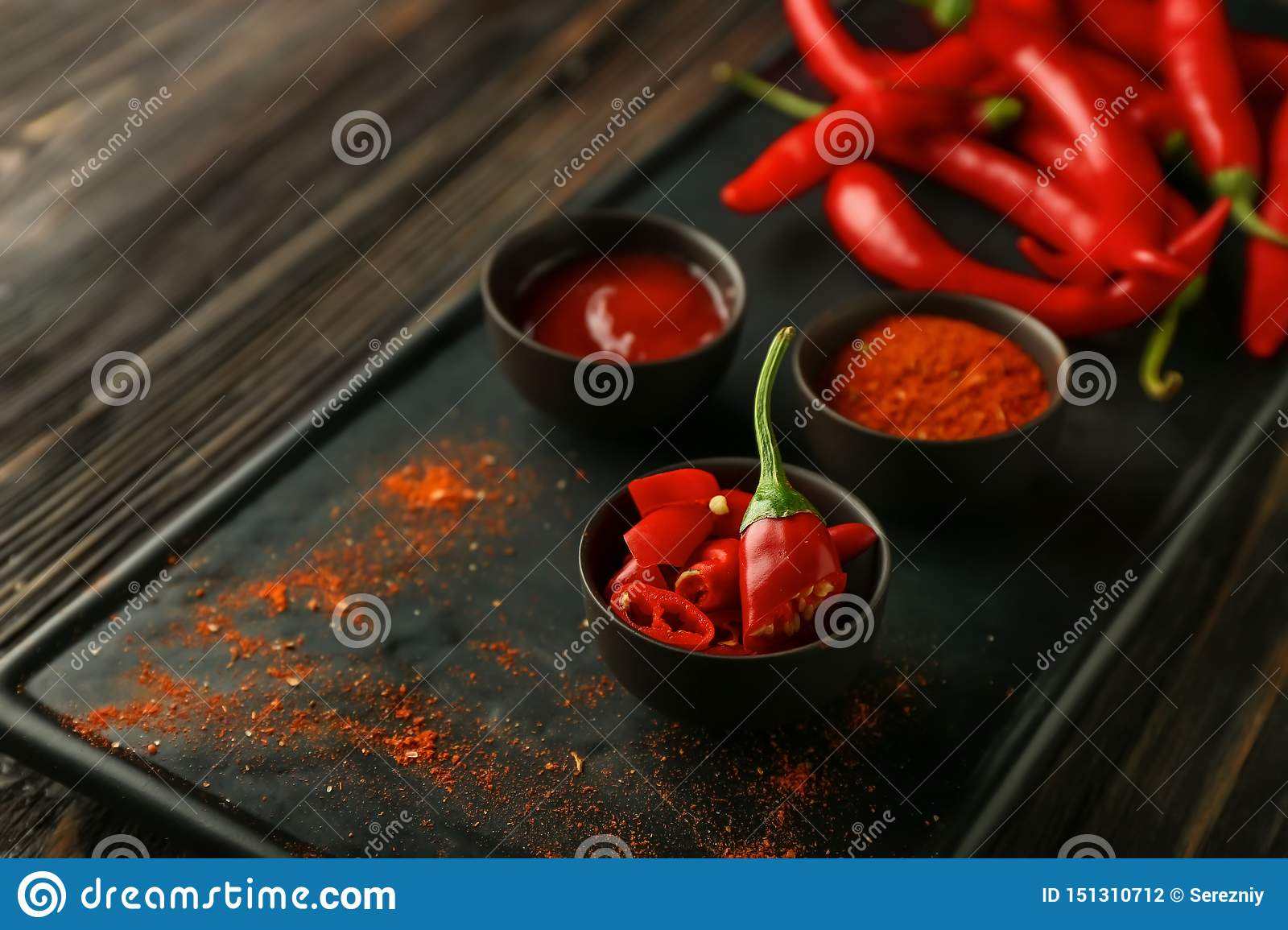 Bowls with red hot chili pepper, powder and sauce on plate, closeup