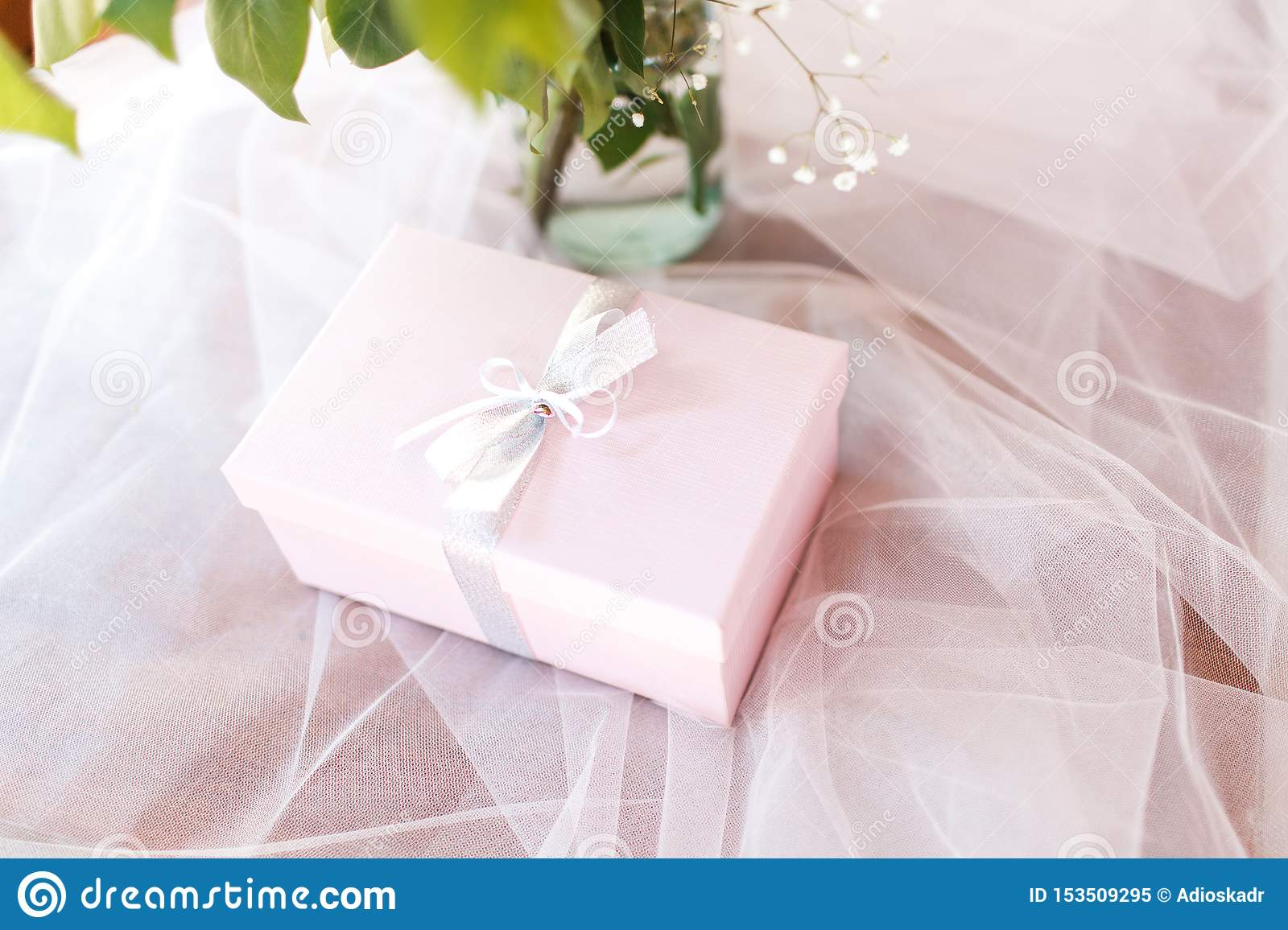 The box with a bow lies on tulle