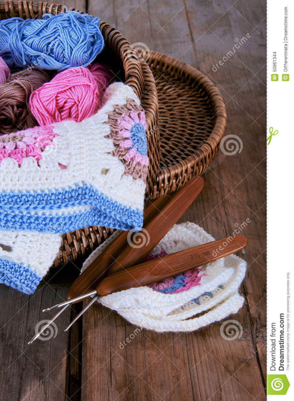 Box of yarn and granny square blanket with crochet hooks