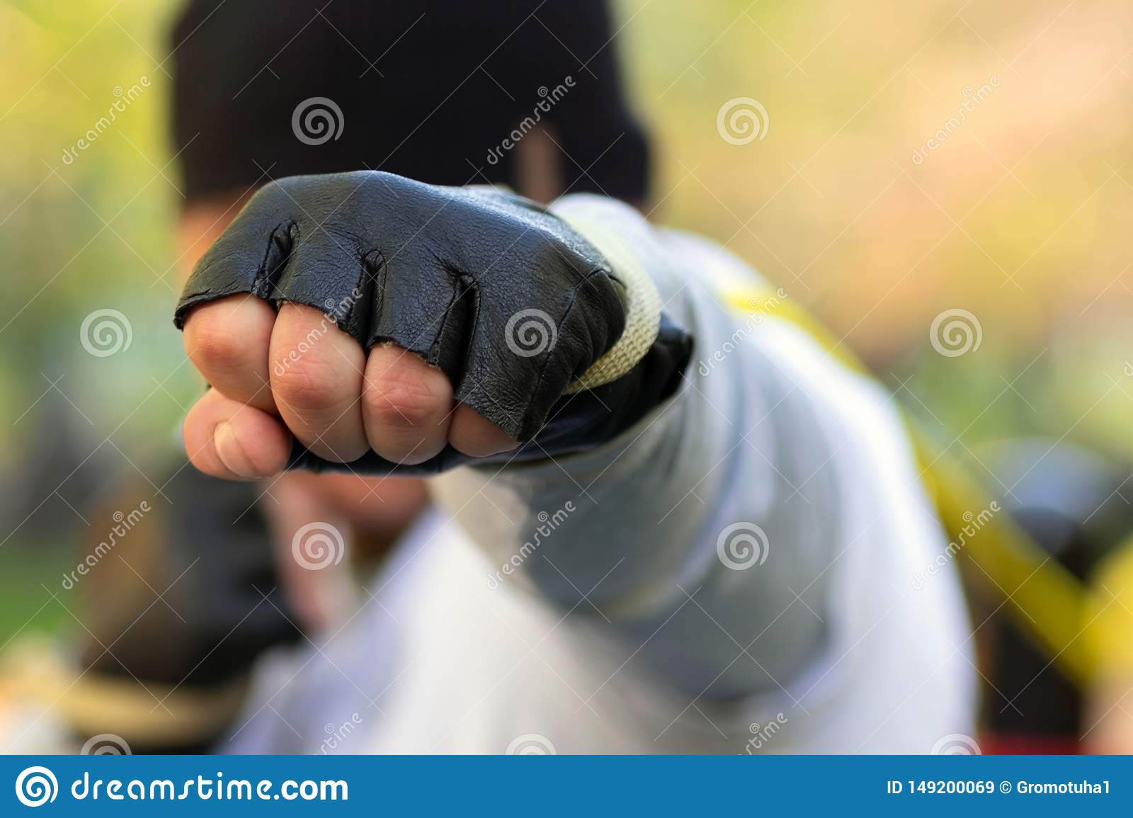Boxer man strikes with his fist in a protective glove at the target. In his fist clamped with great rubber from the trainer