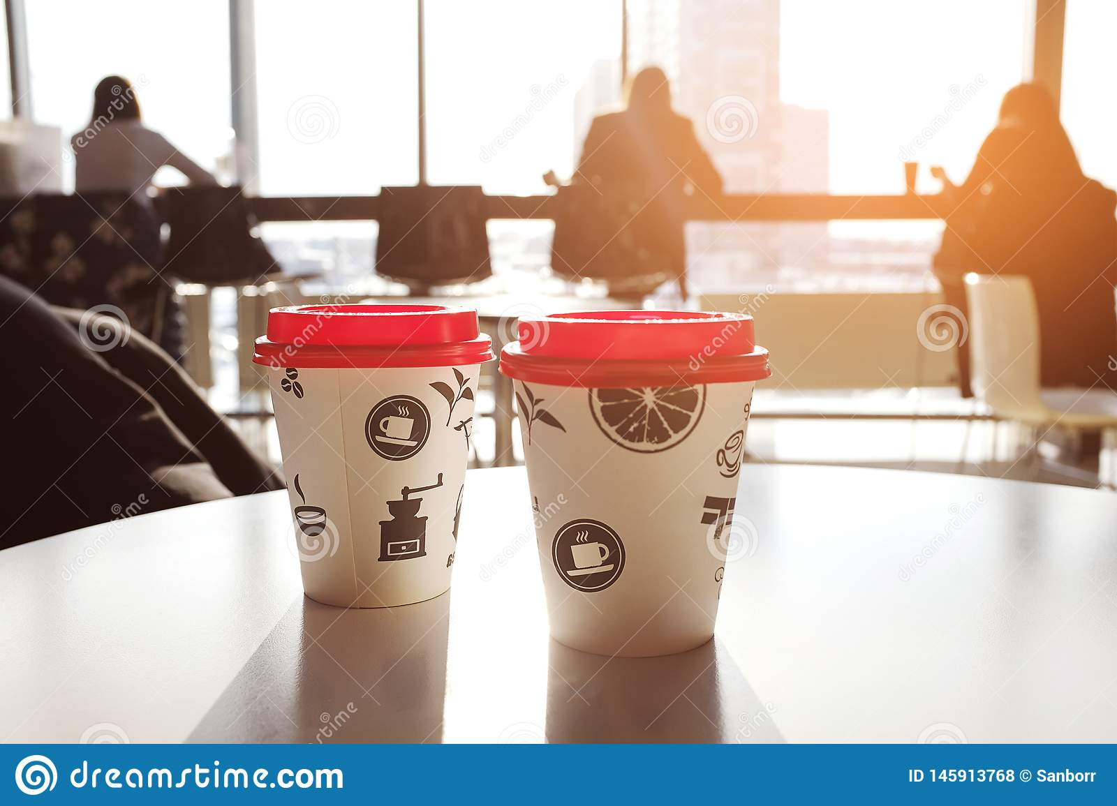2 boxes of paper disposable cups with red led on the table in the cafe. Morning. Coffee for Breakfast. Coffee to go. The shadows